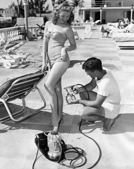 Old image from the 50s showing model getting spray tanned
